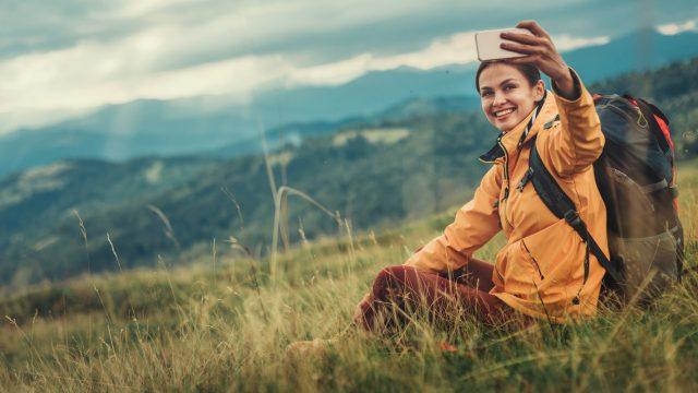 Frau sitzt beim Wandern auf Berghang