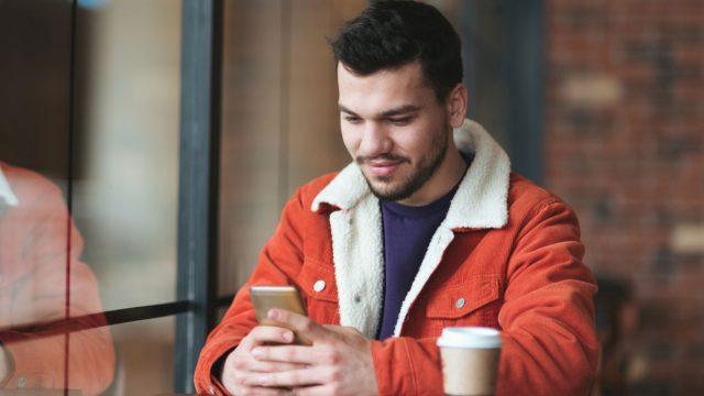 Mann teilt am Smartphone mit Google Chrome eine Webseite.