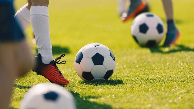 Spieler spielen Fußball auf dem Platz.