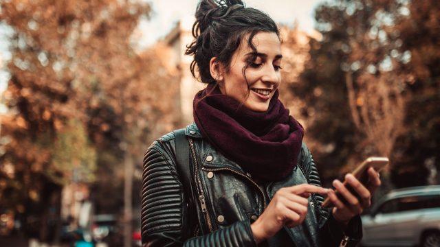 Frau schaltet den Dark Mode von WhatsApp am Smartphone ein.