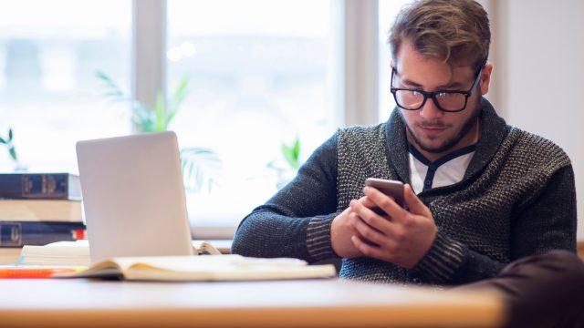 Mann sitzt mit Telefon am Tisch und weist einen Anruf ab