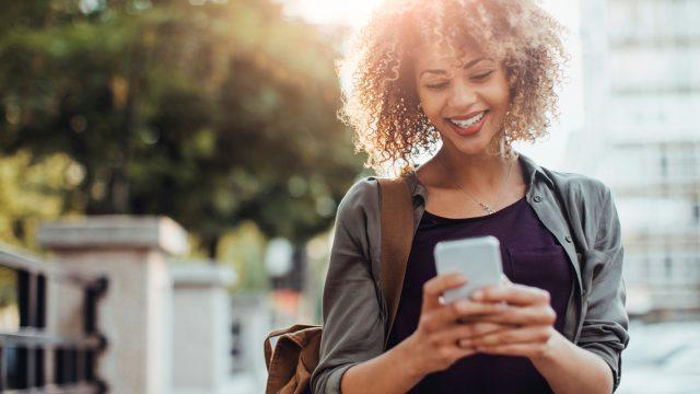 Junge Frau sieht auf Smartphone