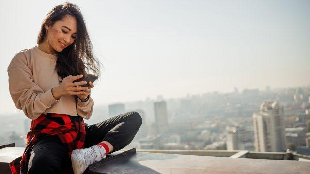 Frau sitzt auf einer Mauer und schaut auf ihr Handy.