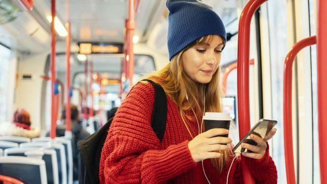 Frau öffnet den Musikplayer unter Android 11 am Handy.