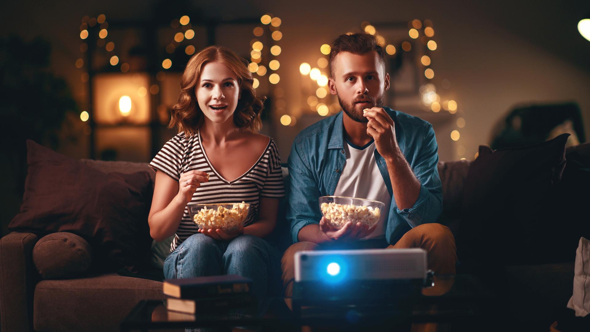 Ein Paar isst Popcorn und schaut TV.