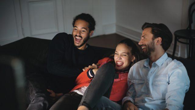 Drei Junge Leute auf dem Sofa freuen sich über die GigaTV-Cable-Senderübersicht