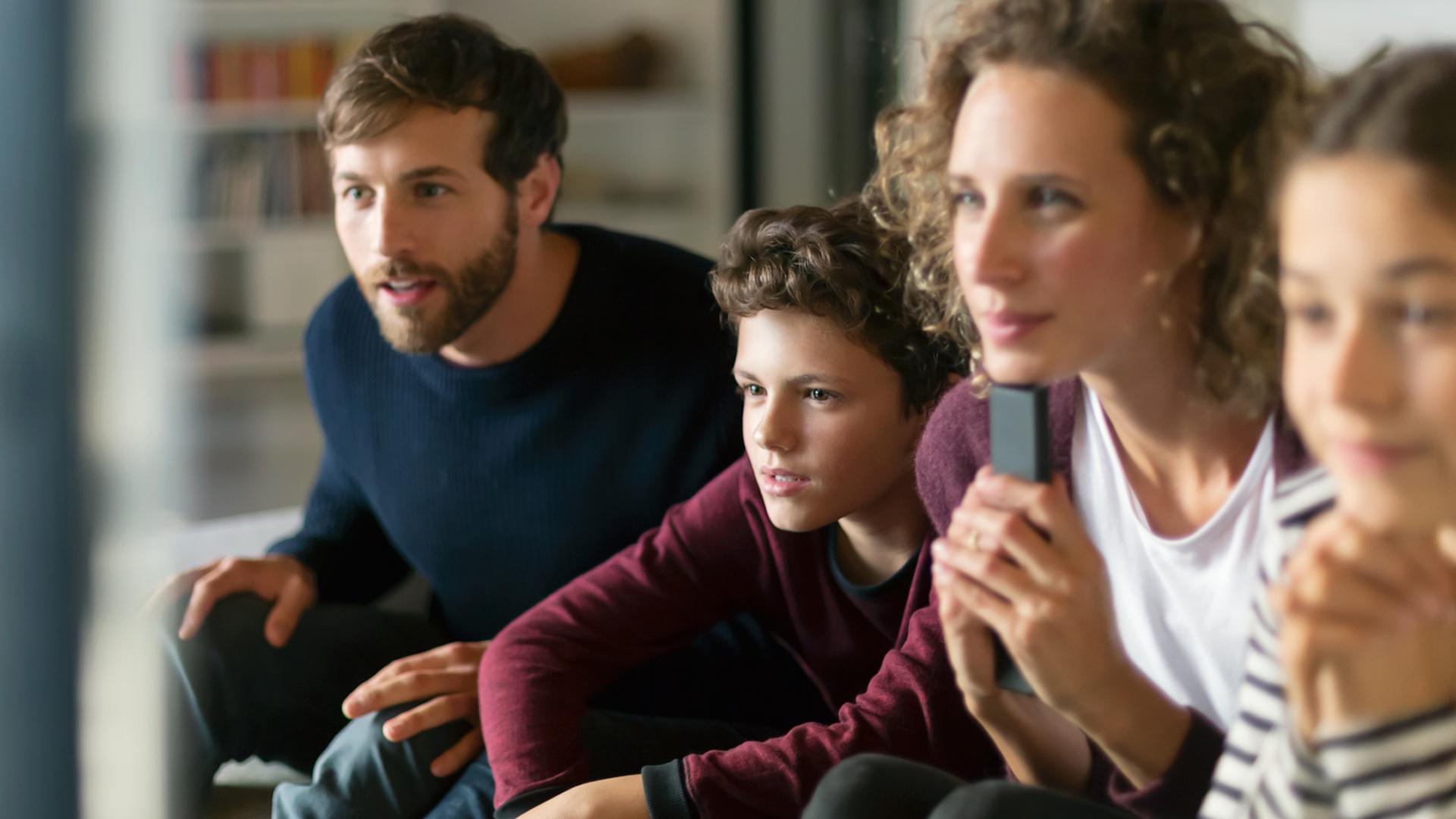 Vater, Mutter, Sohn und Tochter schauen kostenlose GigaTV-Kids-Inhalte