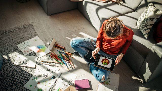 Eine Frau sitzt auf dem Wohnzimmerboden und zeichnet via Tablet.