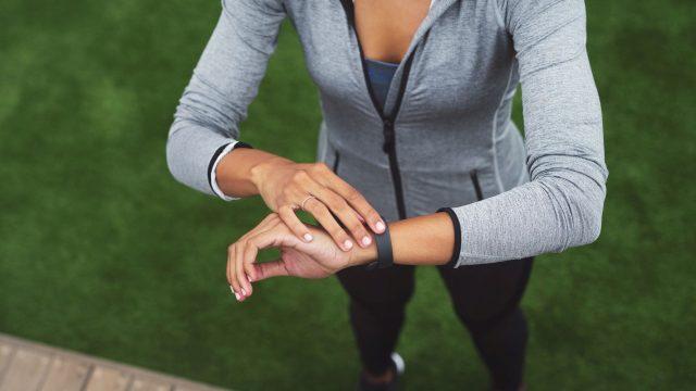Junge Frau trackt mit ihrer Fitbit ihr Workout.