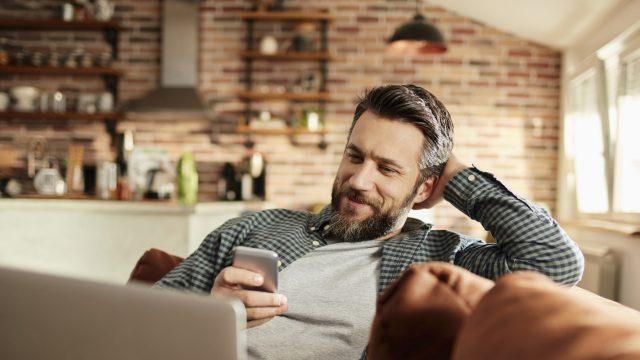 Mann mit Smartphone im Wohnzimmer