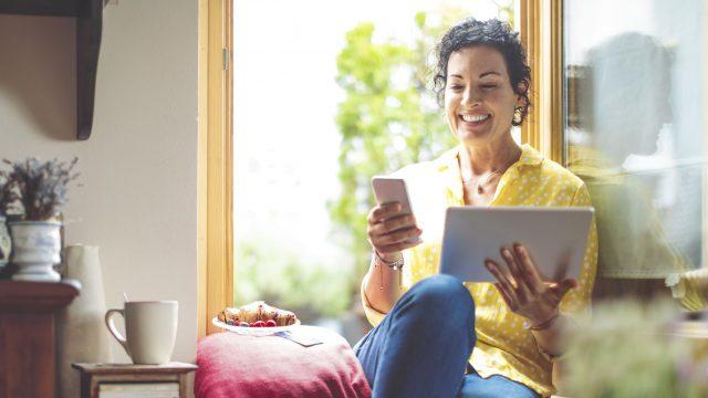 Frau nutzt WhatsApp auf Smartphone und Tablet.
