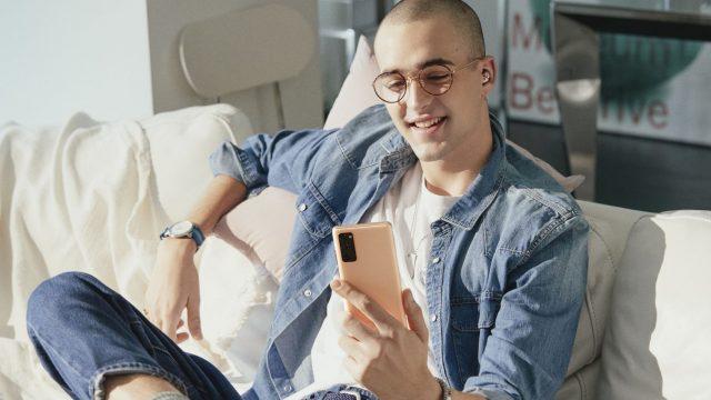 Junger Mann hält Samsung Galaxy S20 FE in der Hand.