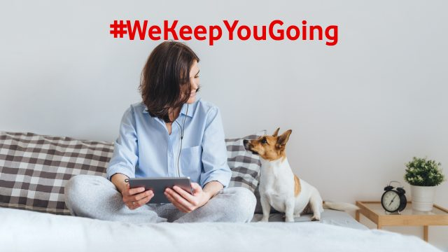 Eine junge Frau sitzt mit ihrem Hund auf dem Bett und nutzt ihr Tablet.