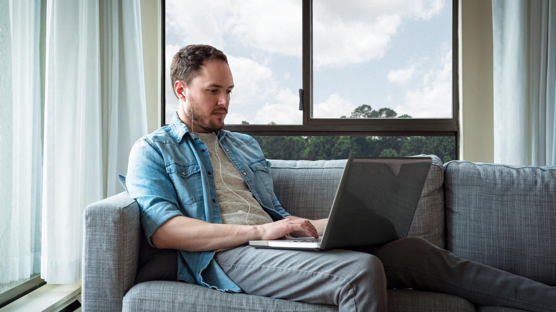Ein Mann telefoniert mit Kopfhörern über seinen Laptop.