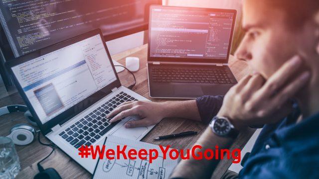 Ein Mann programmiert am Laptop und mit mehreren Bildschirmen.