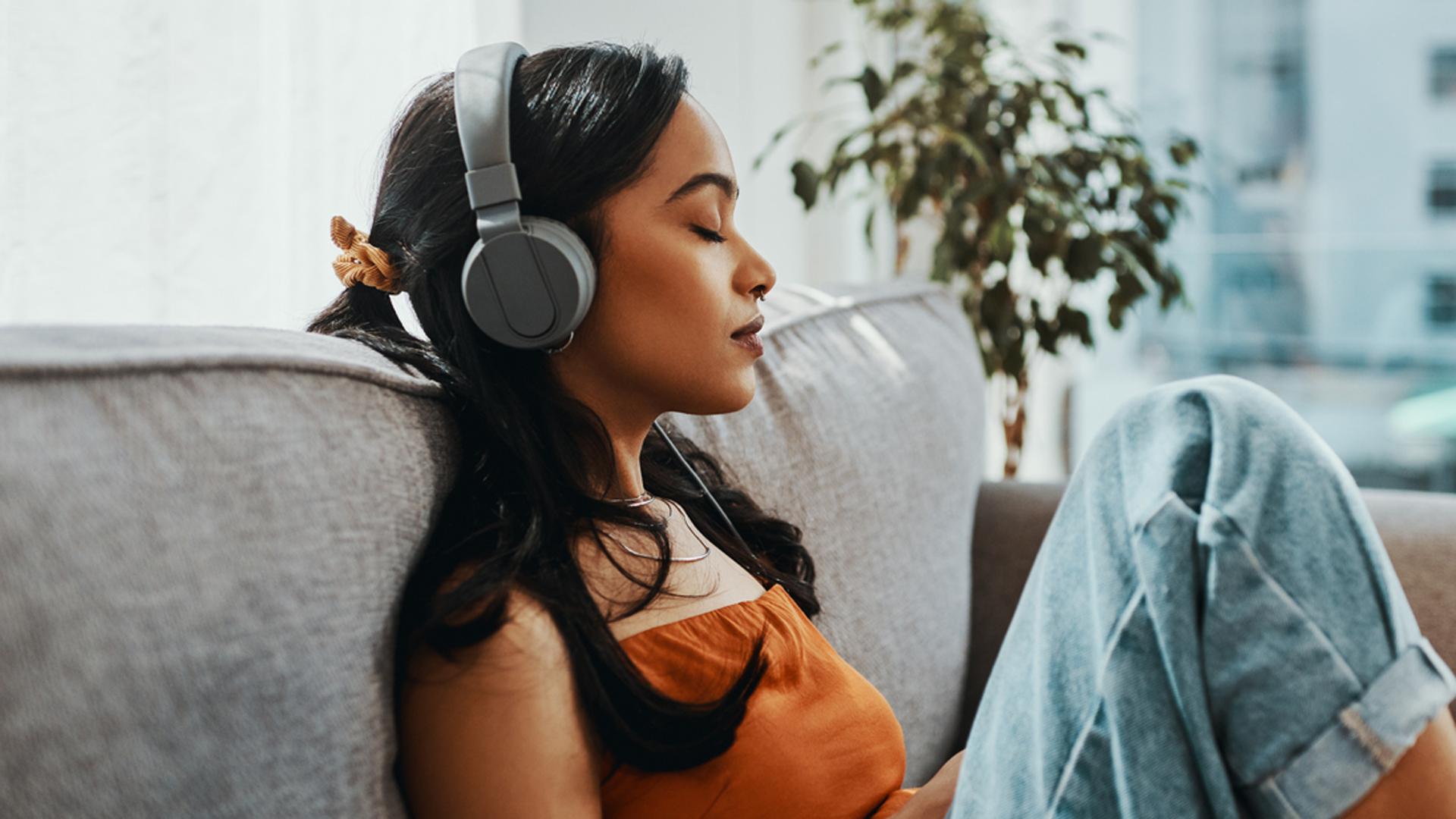 Frau hört mit geschlossenen Augen und Kopfhörern Wissens-Podcasts