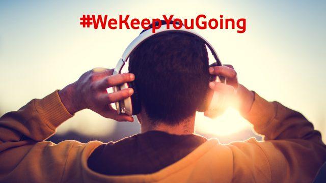 Man von hinten mit Kapuzenpulli und Kopfhörern hört Wissens-Podcasts
