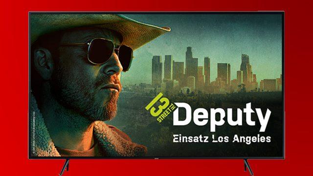 """Deputy Hollister mit Cowboyhut und Sonnenbrille in """"Deputy - Einsatz Los Angeles""""vor der Skyline von LA."""