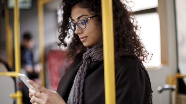 Frau sieht sich am iPhone den Dark Mode von Facebook an.