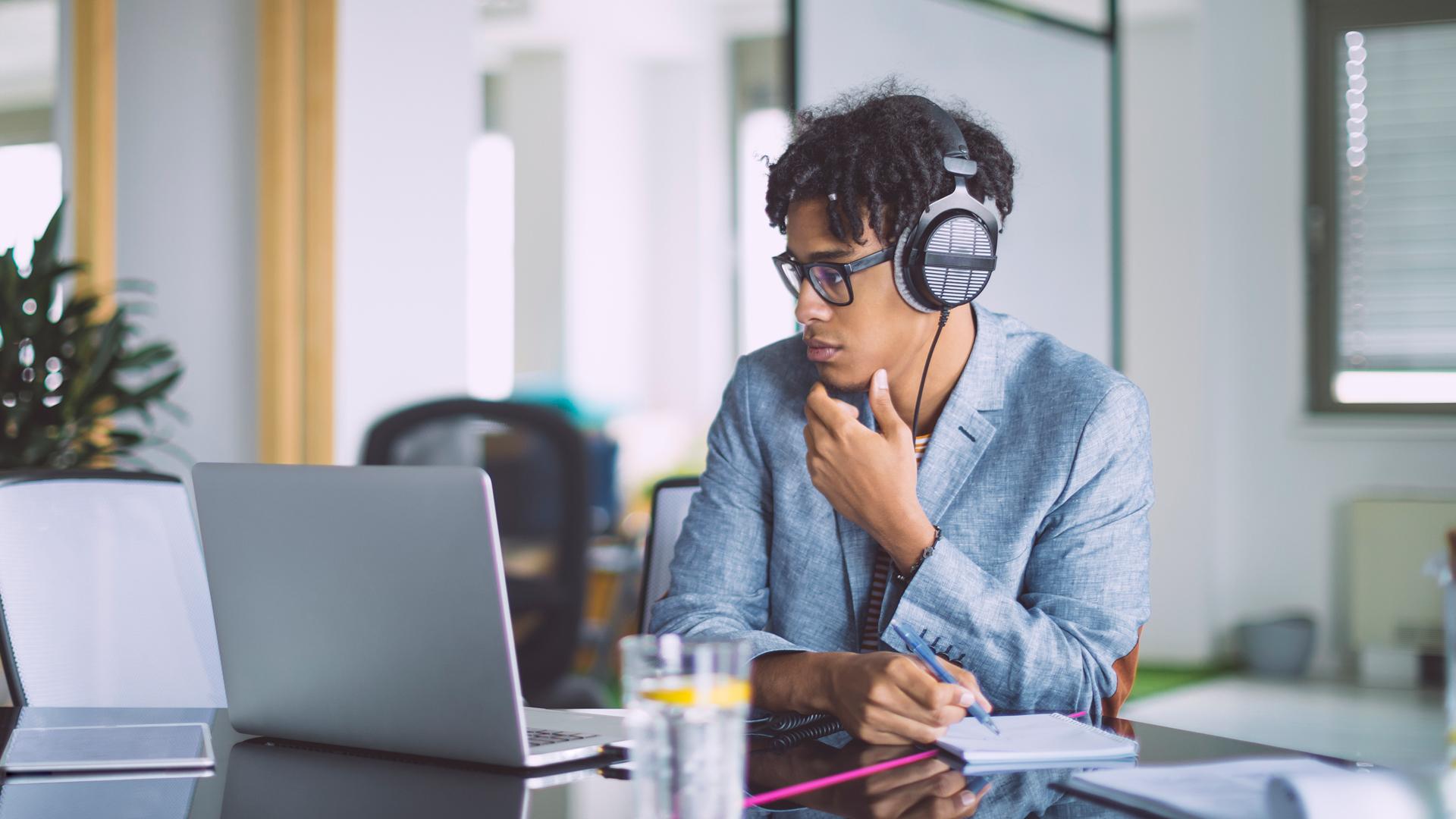 Ein junger Mann trägt Kopfhörer beim Arbeiten am Laptop.