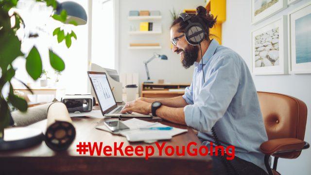Ein junger Mann trägt Kopfhörer beim Arbeiten am Laptop zuhause und lacht dabei.
