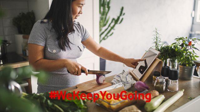 Eine Frau schneidet Gemüse in der Küche und nutzt ihr Tablet, um ein Gericht per Anleitung zuzubereiten.