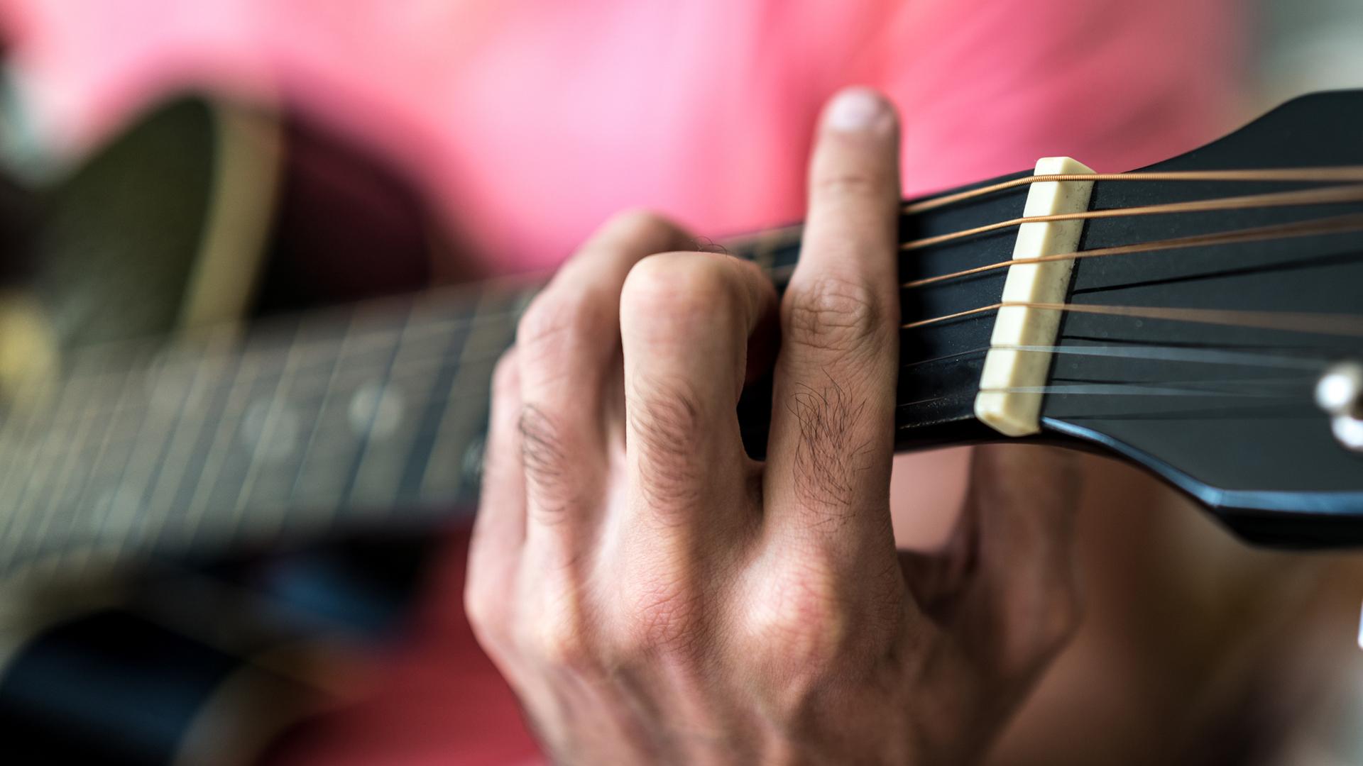 Hand an einer Gitarre