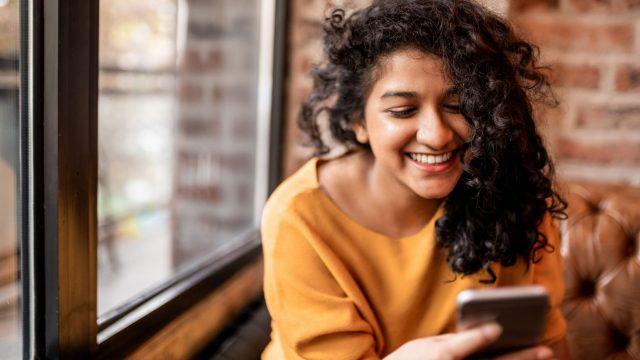Frau überwacht Zyklus in der Fitbit-App am Smartphone