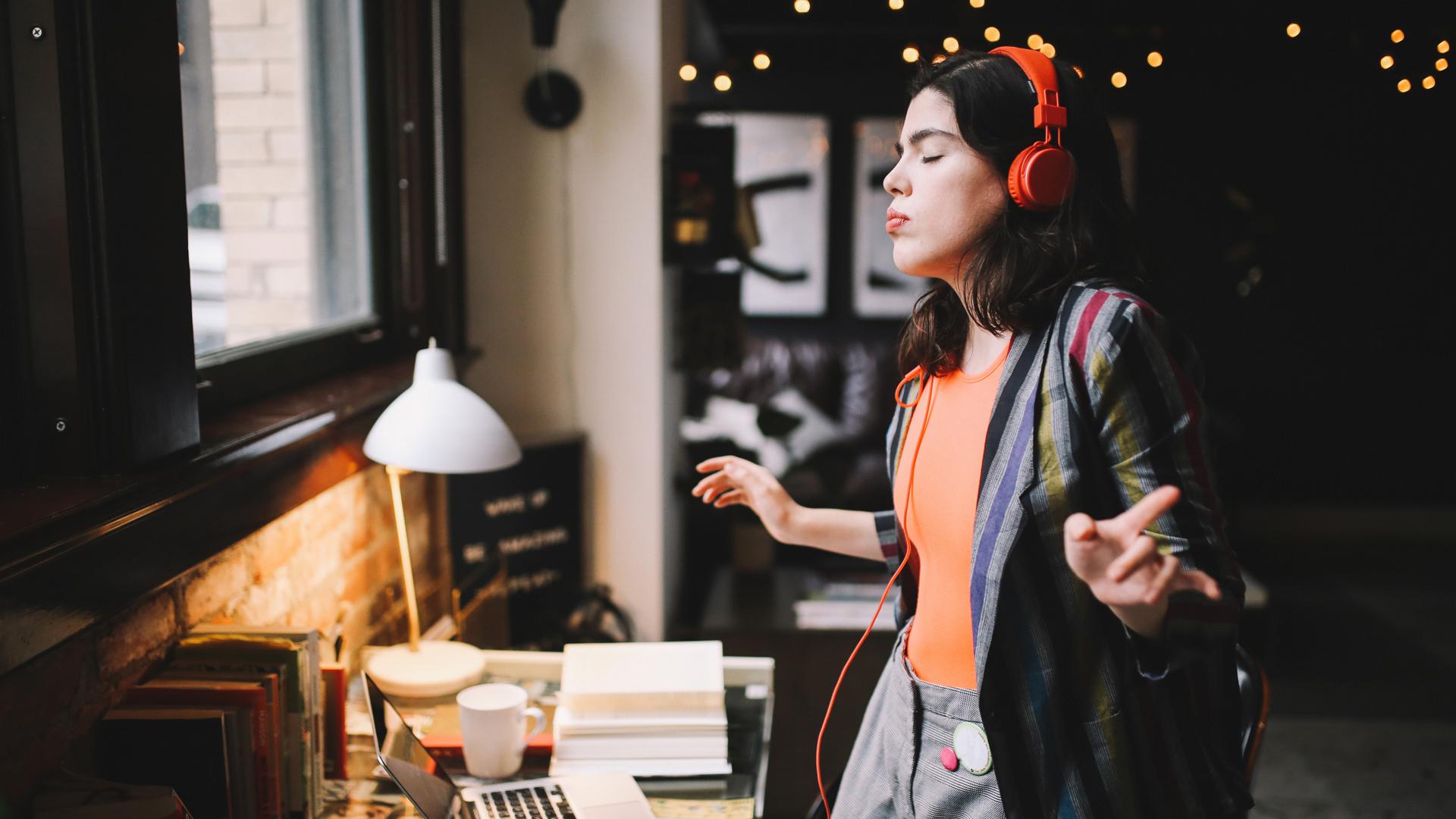 Eine junge Frau trägt zuhause vor ihrem Laptop Kopfhörer und tanzt im Stehen zu Musik.