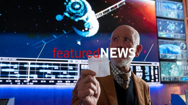 """John Malkovich in der neuen SciFi-Comedy """"Space Force"""" mit einem Zettel in der Hand und vor mehreren Bildschirmen, die ein Raumschiff zeigen."""