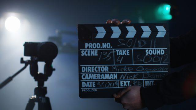 Eine Filmklappe, die beim Dreh einer Filmszene zugeklappt wird, im Hintergrund eine Kamera.