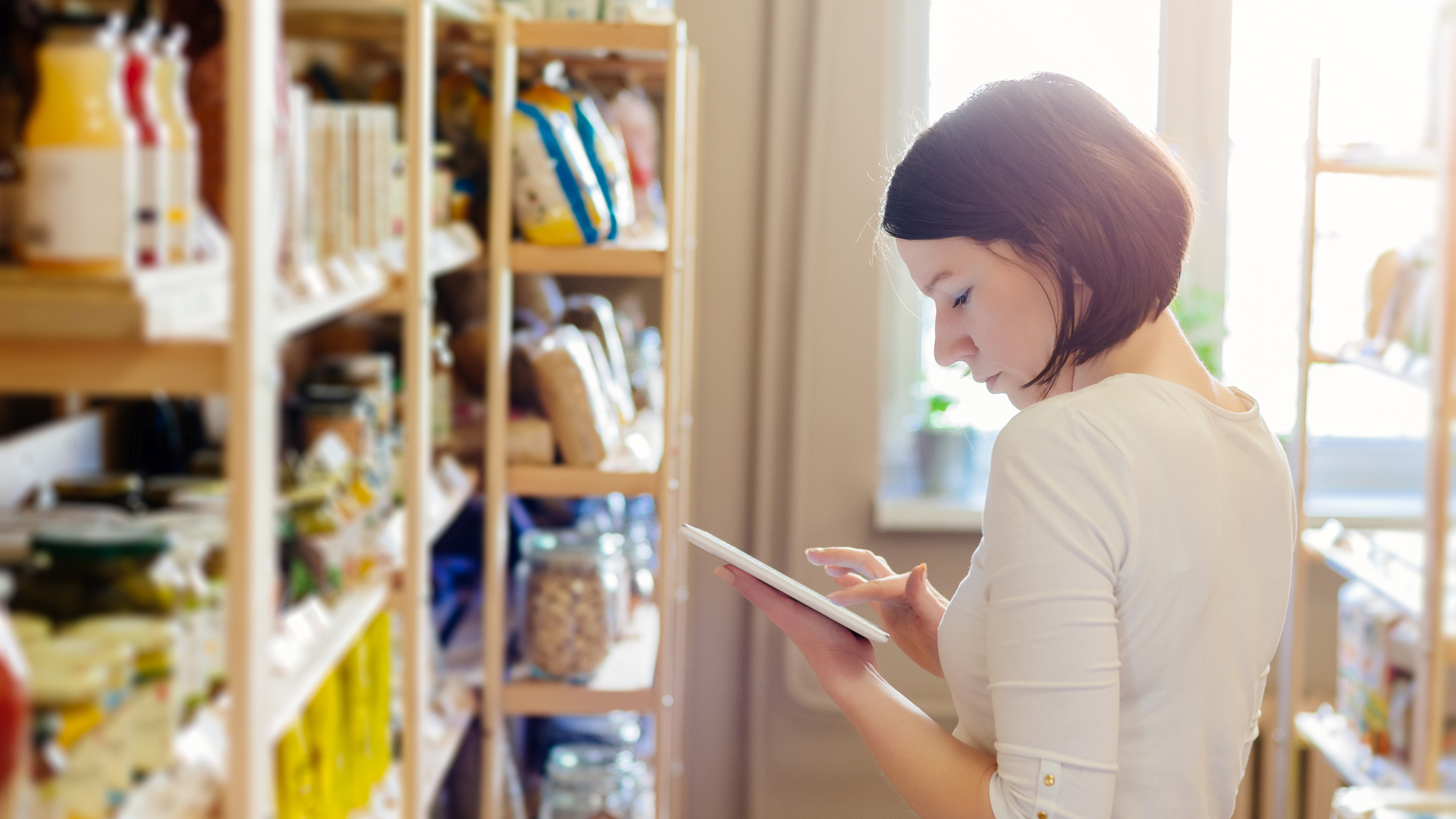 Eine Frau steht mit ihrem Tablet vor einem Regal ihres Lokalgeschäfts.