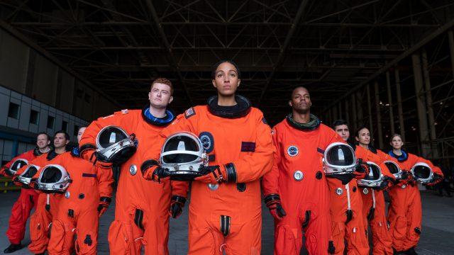 """Ausschnitt aus der neuen SciFi-Comedy """"Space Force"""", zu sehen sind Astronauten in orangen Raumanzügen mit ihren Helmen in der Hand."""