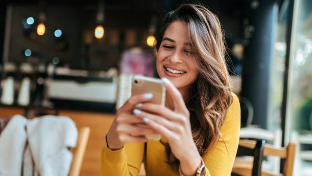 Frau lachend mit Smartphone
