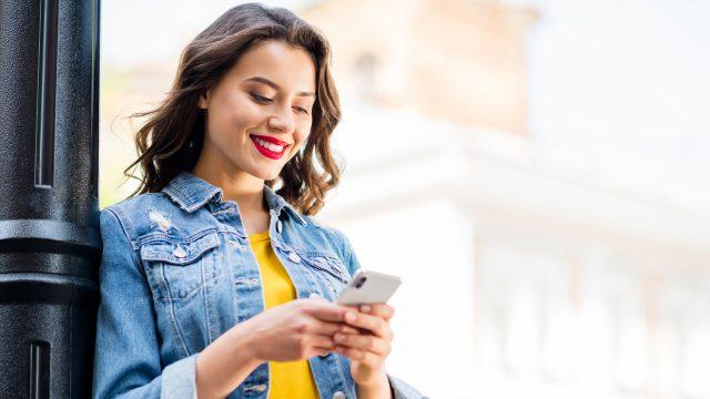 Frau mit Smartphone an Laterne