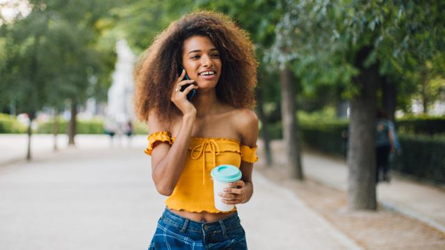 Junge Frau in gelbem Oberteil spaziert durch Park und telefoniert dabei mit Vodafone Crystal Clear