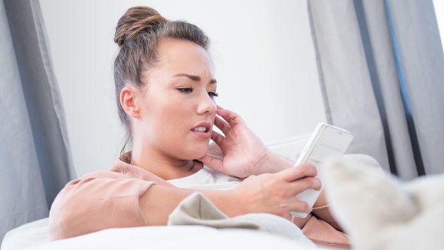Eine Frau blockiert am Smartphone eine Person bei Facebook