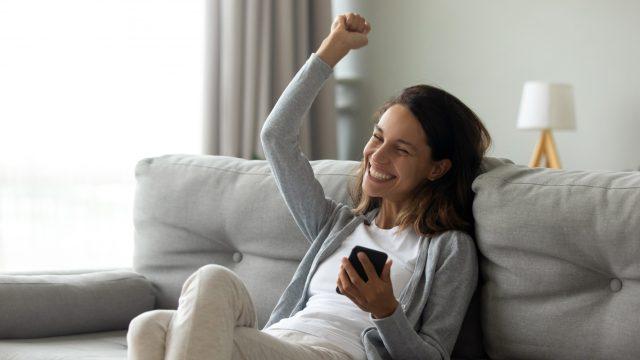 Frau mit Smartphone begeistert