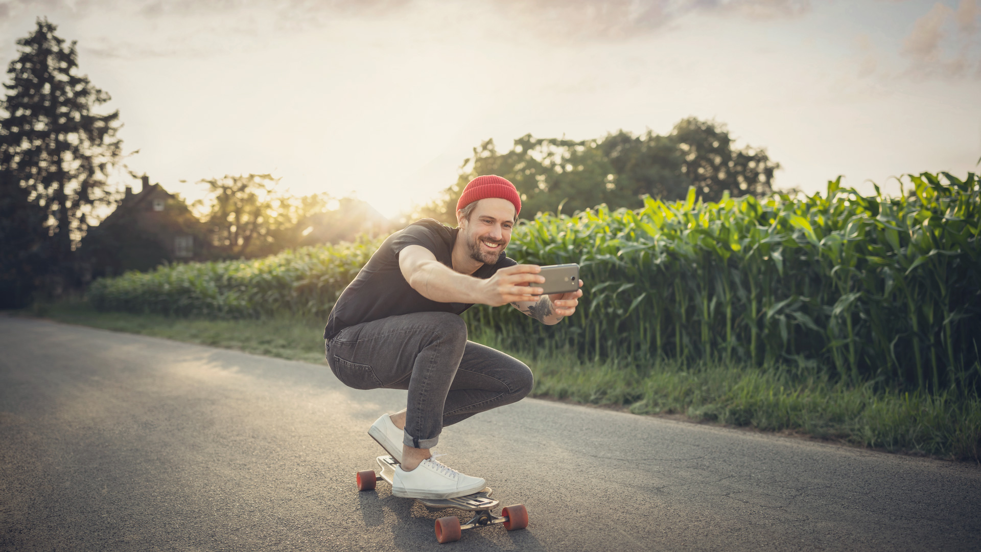Ein Mann fährt mit seinem Skateboard an einem Feld vorbei und nimmt sich dabei auf.