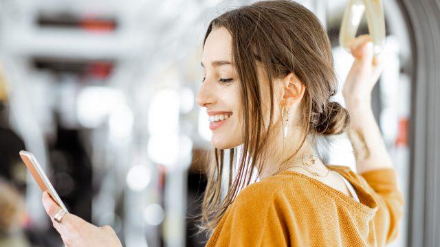 Frau mit Smartphone in U-Bahn