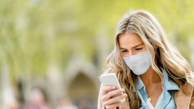 Eine junge Frau trägt einen Mundnasenschutz und schaut auf ihr Smartphone.