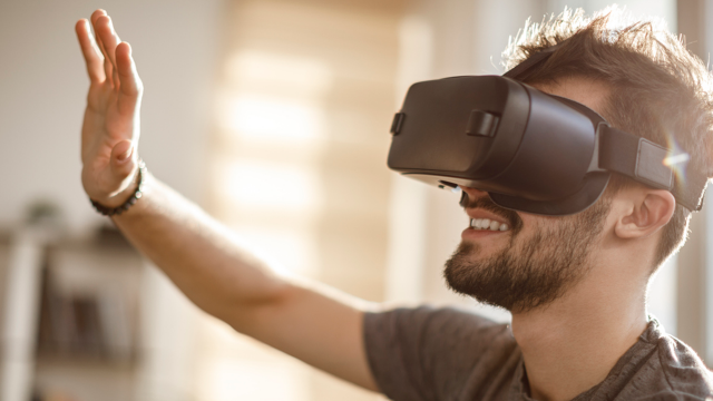 Junger Mann mit VR-Brille spielt Virtua Sonic