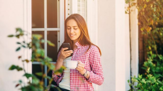 Junge Frau stellt HomeKit am iPhone ein.