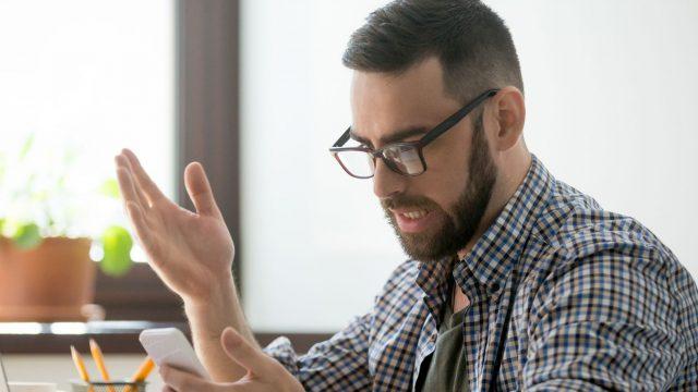 Mann schaut wütend auf sein Smartphone.