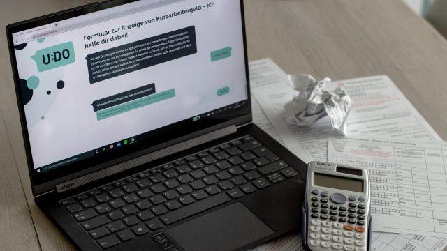 Ein Laptop, auf dessen Bildschirm der Chatbot UDO zur Beantragung von Kurzarbeitergeld zu sehen ist, daneben Unterlagen und ein Taschenrechner.