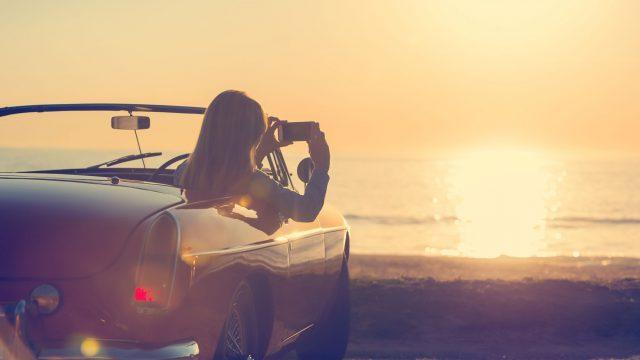 Frau fotografiert aus dem Auto den Sonnenuntergang