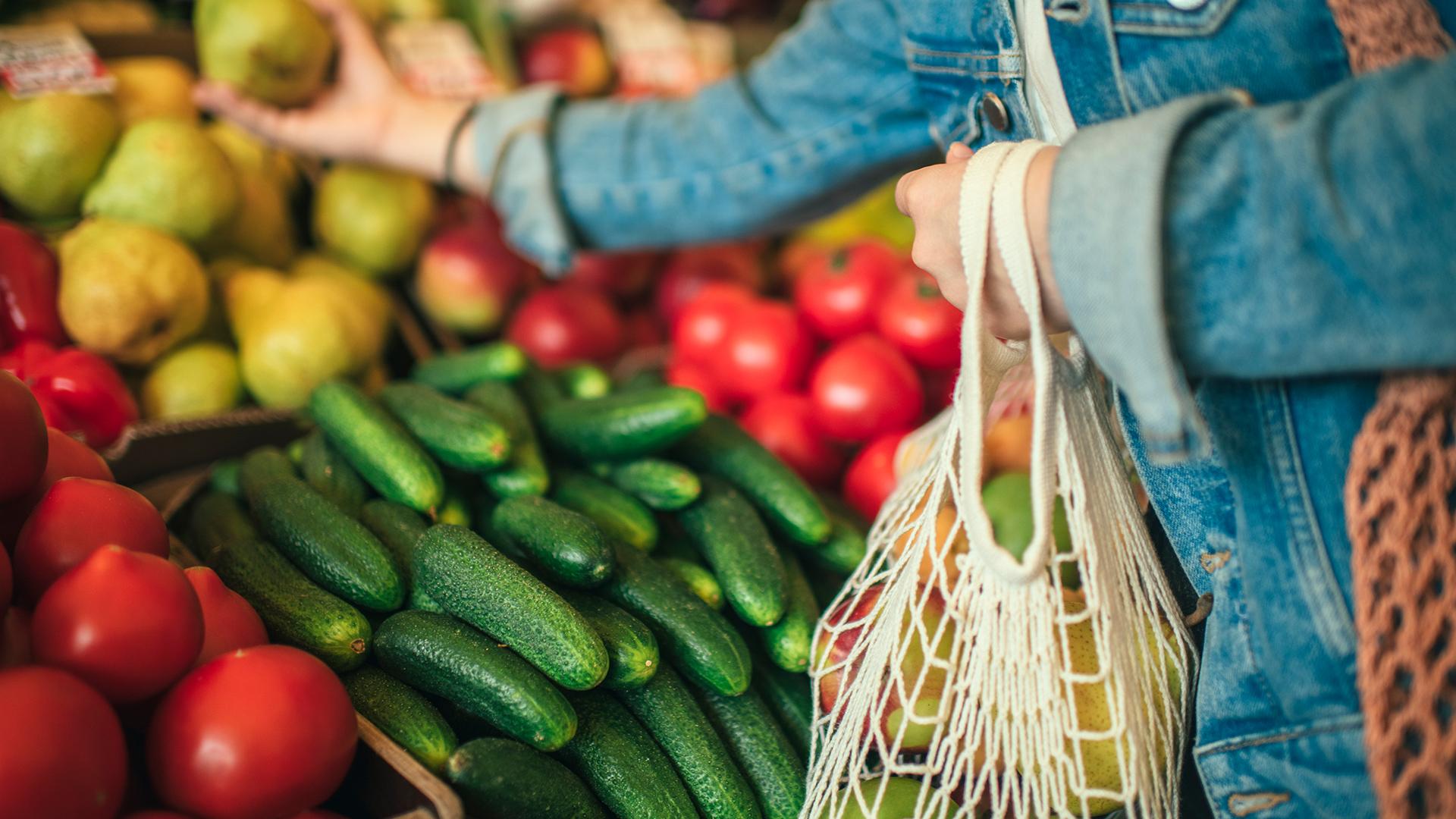 Eine Frau packt im Supermarkt Gemüse in ihr Einkaufnetz.