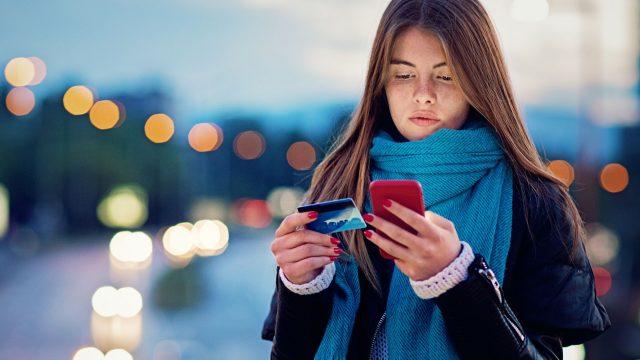 Frau richtet Google Pay mit Smartphone und Kreditkarte ein.
