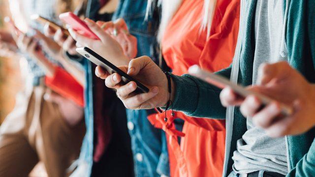 Mehrere nebeneinanderstehende Leute halten Smartphones in der Hand
