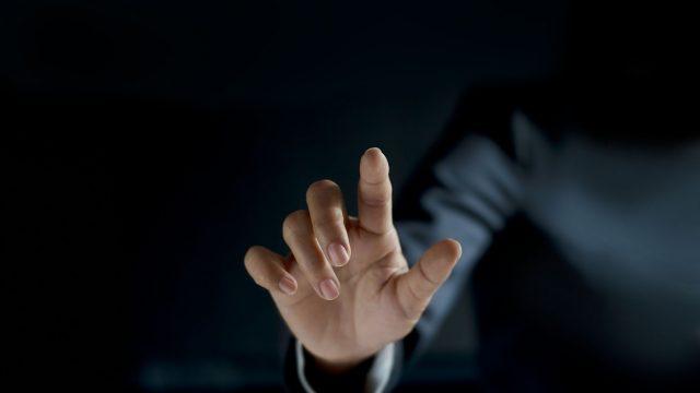 Eine Hand ragt aus der Dunkelheit in Richtung des Betrachters.